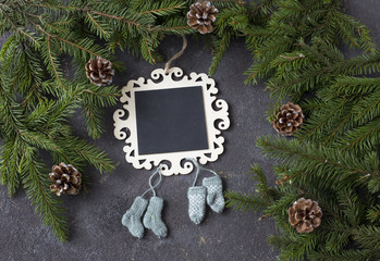on a festive background a plate for notes, cones, branches of pine and mittens, socks