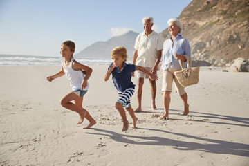 Grandparents Running Along Beach With Grandchildren