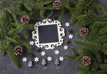 on a festive background a plate for notes, cones, branches of pine and christmas decoration