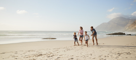Parents Running Along Beach With Children On Summer Vacation Wall mural