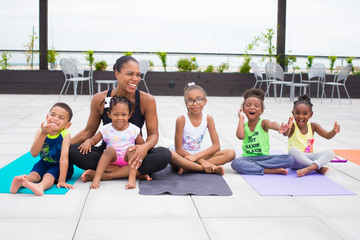 Woman sitting with children on yoga mats
