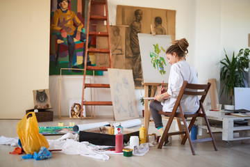 Artistic girl sitting in studio and paint on easel.