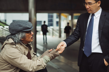 Business man give a money to homeless people
