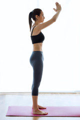 Sporty young woman doing hypopressive abs indoor.