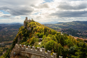 Rocca della Guaita (Castle in San Marino) guarding over the valley under the cloudy mantle of the sky. Colourful landscape with sun and clouds