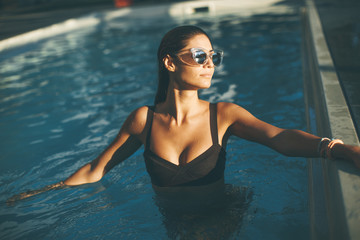 Young woman in the outdoor swimming pool
