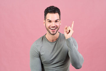 attractive white-skinned athletic man smiles happily and raises his finger, showing that he had a great idea.