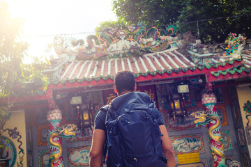 men backpacker looking at a temple in Bangkok , Thailand , Southeast asia .