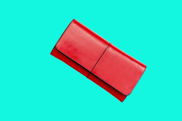 A red purse on a blue background, trend of minimalism, top view, flat lay.