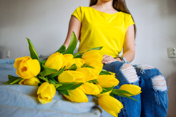 woman hold bouquet of yellow tulips. romantic flowers knees wide