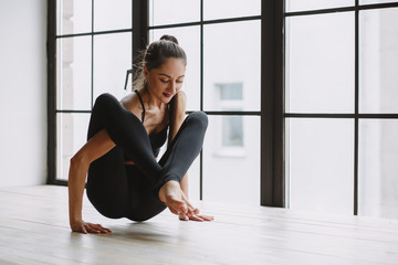 Young woman doing yoga at light window