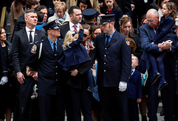 Eileen Davidson carries her daughter Emily as Emily waves, while the casket with her father, New York City Fire Department Lieutenant Michael R. Davidson, is carried from St. Patrick's Cathedral following his funeral in Manhattan in New York City