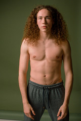Attractive and stylish guy with curly hair and a sports figure