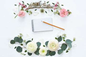 Top view and flat lay with notebook and frame of flowers on white background