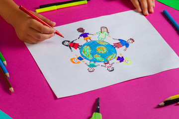 Kids draws with pencils and markers peace in the world. Child drawing the friendship of the peoples of the planet.