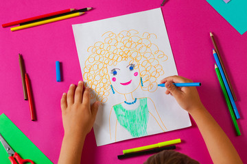 Child draws picture of mom for mother's day. Little girl made a drawing with pencil and marker.
