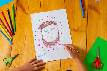 Child draws a portrait of his dad on father's day. The little boy did the drawing with pencil and marker.