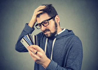 stressed man looking at too many credit cards