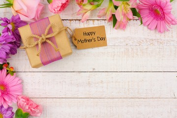 Corner border of flowers with Mothers Day gift and tag against a rustic white wood background