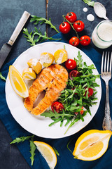 Grilled salmon with arugula and cherry tomato salad and potatoes on blue background