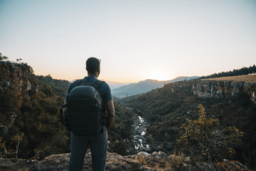 Rear view of man with backpack standing on mountain against clear sky during sunset