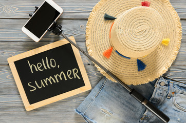 Womens clothing, accessories (denim shorts, straw hat, cellphone, selfie stick, chalkdoard) on grey wooden background. Text Hello summer. Trendy fashion outfit. Shopping, travel concept.  Flat lay