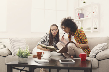 Two female friends preparing for exam at home