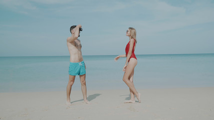 Young happy couple in swimwear having fun taking photo on their beach tropical holiday