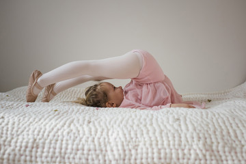 Side view of girl in ballet costume dancing on bed at home