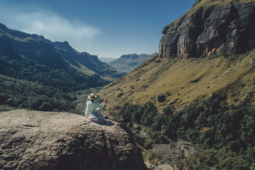 Rear view of woman looking at view while sitting on mountain against sky