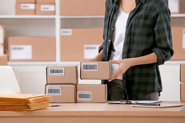 Young woman preparing parcels for shipment to client in home office