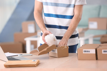 Young man preparing parcel for shipment to client at home