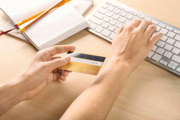 Woman with credit card using computer at table