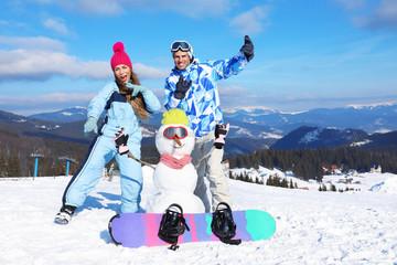 Happy couple with snowman having fun at ski resort. Winter vacation