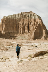 Rear view of female hiker with backpack exploring desert against rock formations during sunny day