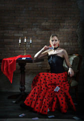 sexy passionate Spaniard near an old table with candles and playing cards on a brick wall background. Beautiful girl in a red dress.  Dancer flamenco woman