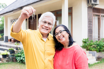 Portrait of a happy senior man posing with his wife while holding the keys of a residential house