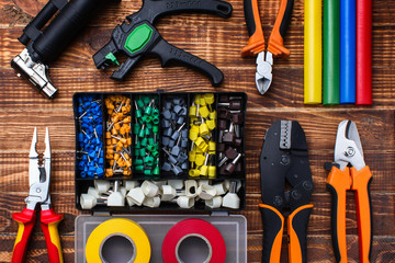 background of professional electrician tools: cable lugs in the organizer box, insulating tape, earplugs, cutters, tips, burnerpuller insulation, on a wooden board