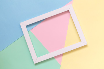 Abstract flat lay of picture frame against multicolored background minimalistic concept.
