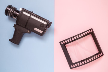 Flat lay of vintage video camera and blank frame in form of analog film on multicolored background minimalistic concept.