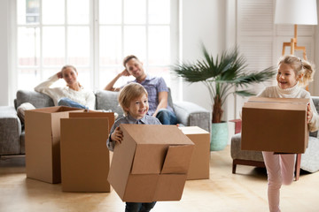 Cute small kids carrying boxes playing together on moving day concept, active happy boy and girl chasing each other in living room, excited children having fun helping parents pack unpack in new home