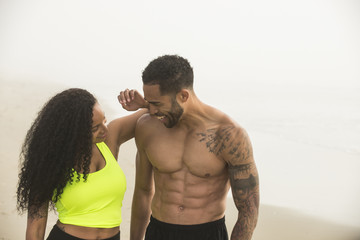 Muscular man and young woman standing on coastal beach and looking at each other while smiling, Hampton, New Hampshire, USA