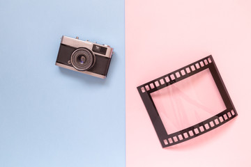 Flat lay of vintage camera and blank frame in form of analog film on multicolored background minimalistic concept.