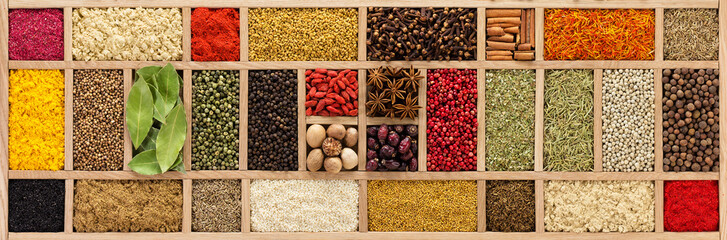 Fototapete - background of various spices and herbs. Seasoning in  wooden box, top view