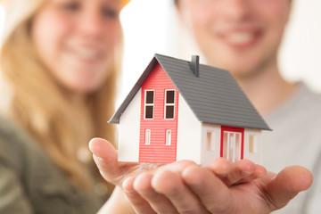 Junges Paar freudig lachend mit einem Modell-Haus, Eigenheim