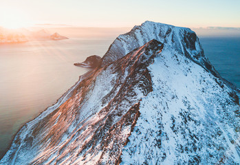 Norwegian winter sunny mountain landscape blue sky view with mountains, fjord, Norway, Ryten peak - famous mountain in Lofoten Islands, Moskenes municipality, Nordland, shot from drone