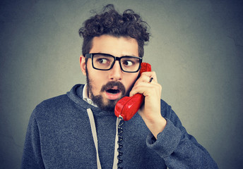 Shocked man receiving unexpected news over the phone