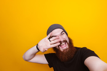 Cheerful young bearded man holding hand on face and taking selfie