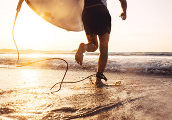 Man surfer run in ocean with surfboard. Active vacation, health lifestyle and sport concept image Wall mural