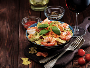 Delicious farfalle pasta with shrimps on wooden background. Mediterranean cuisine